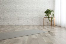 Unrolled Grey Yoga Mat On Floo...