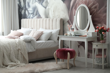 Stylish bedroom interior with elegant dressing table and floral wallpaper