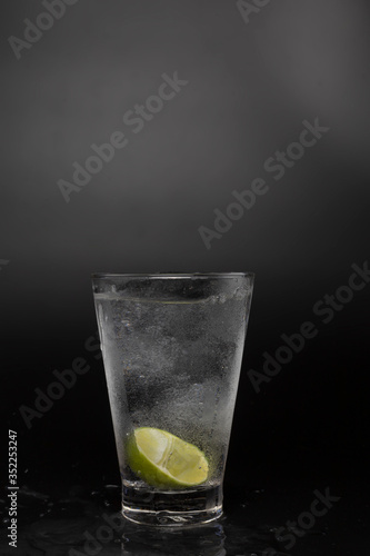 Soad water in glass with lime on black background Canvas Print