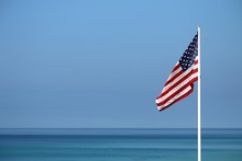 Close-up Of American Flag Against Clear Blue Sky