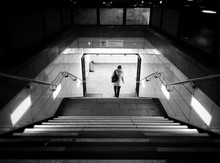 Rear View Of Woman Moving Down On Steps At Night