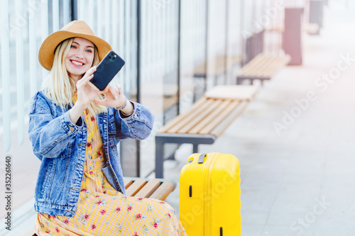 Stylish young woman blogger influencer traveler in straw hat makes selfie while sitting at a public bus stop Canvas Print