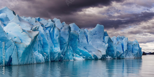 Fotografiet Scenic View Of Glacier By Sea Against Sky