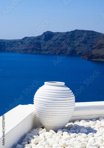 Obraz Santorini, Greece. White terrace with ceramic pot and pebbles against blue sea and sky background. - fototapety do salonu