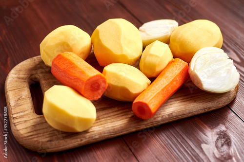 Fototapeta peeled raw potatoes, carrots, onions on a wooden background. Preparing vegetables for cooking. obraz