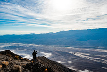 Man Taking A Picture On Mobile Phone At Dante's View Viewpoint On The North Side Of Coffin Peak, Along The Crest Of The Black Mountains, Death Valley, USA.