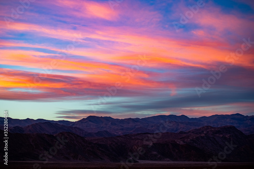 Obraz A stunning sunset or sunrise scene of silhouette mountain peaks and purple ridges with the twilight background, the blue sky and the pink-yellow skyline - fototapety do salonu