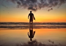Silhouette Man Carrying Surfboard On Beach At Dusk