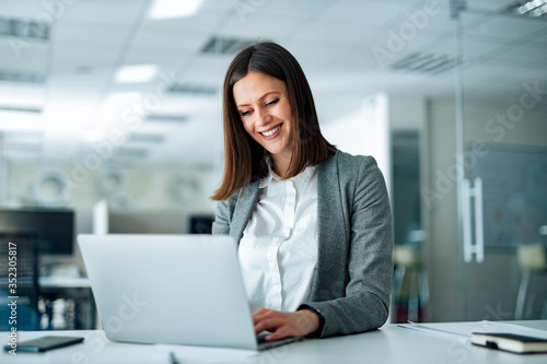 Leinwand Poster Portrait of smiling brunette businesswoman working on laptop in the office