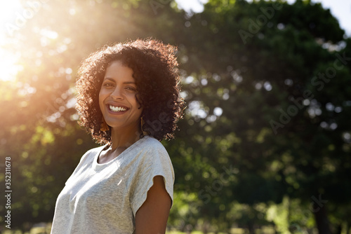 Woman standing in a park in the summer and smiling