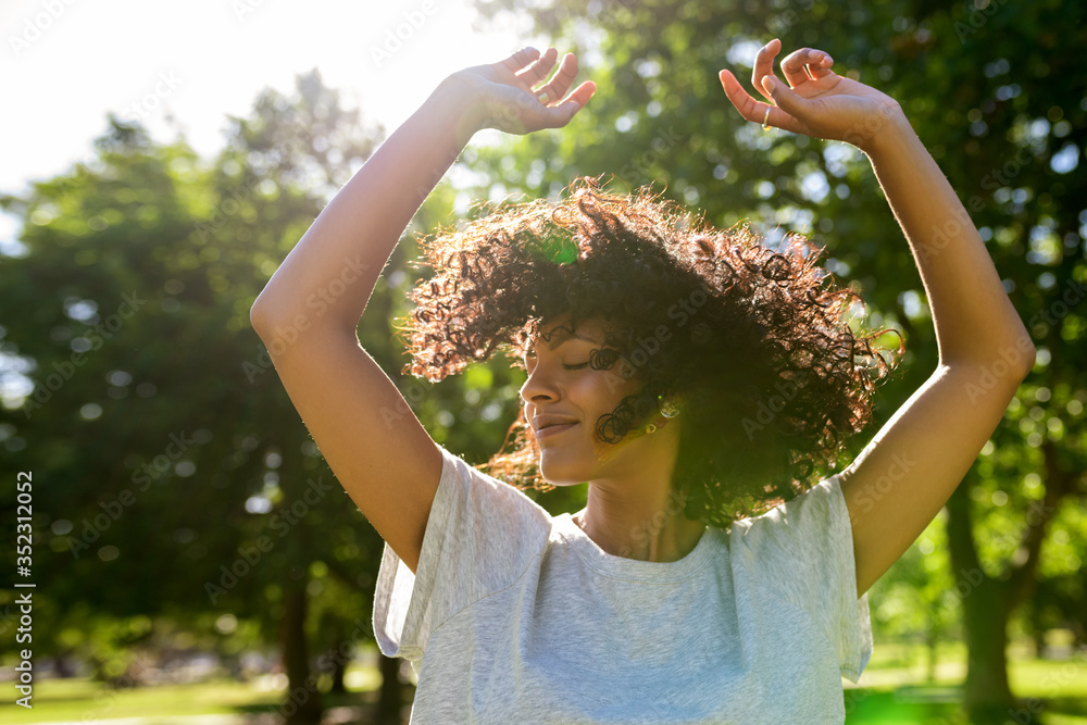 Fototapeta Carefree woman dancing in a park on a sunny afternoon