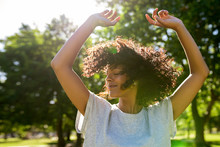 Carefree Woman Dancing In A Park On A Sunny Afternoon