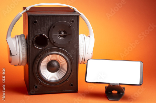 White headphones on speaker and smartphone, music online concept, mockup, isolate on orange #352314626