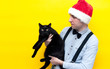 canvas print picture - handsome man in red christmas santa hat holding cute scared big fat black cat on yellow background with copy space