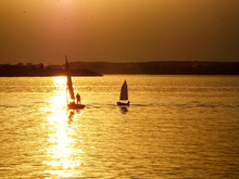 Silhouette People In Boats Sailing On Sea At Sunset