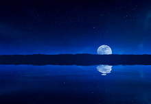 Reflection Of Moon In River Against Star Field At Night