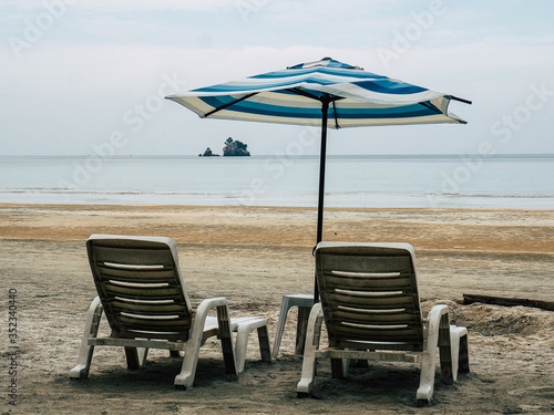 Fotografiet Deck Chairs On Beach Against Sky
