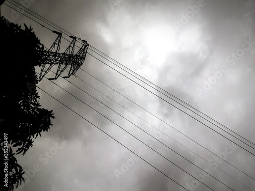 Fotografie, Obraz Low Angle View Of Tree And Electricity Pylon Against Cloudy Sky