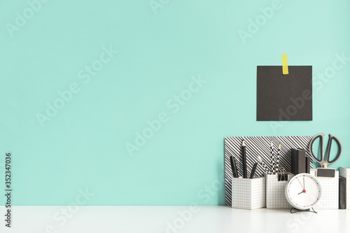 Fototapeta Creative desk with a blank picture frame or poster, desk objects, office supplies, books, and plant on a pastel green background.  obraz