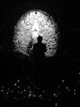 Silhouette Man Praying Against Illuminated Virgin Mary Statue