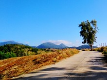 Scenic View Of Road By Mountains Against Clear Blue Sky