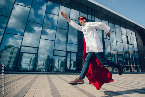 Fototapeta medic superhero hurries to the sick city resident. obraz