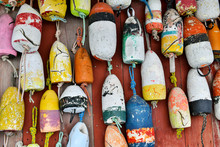 Colorful Lobster Trap Marker Buoys On Wall