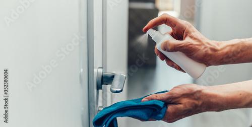 Obraz close up. employee spraying an antibacterial spray on the door handle. - fototapety do salonu