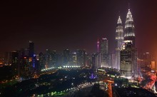 Illuminated Petronas Twin Towers With Cityscape Against Sky At Night