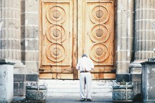 Rear View Of Man Standing In Front Of Closed Wooden Church Door