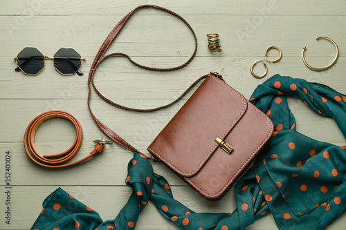 Fototapeta Stylish bag with female accessories on color wooden background obraz