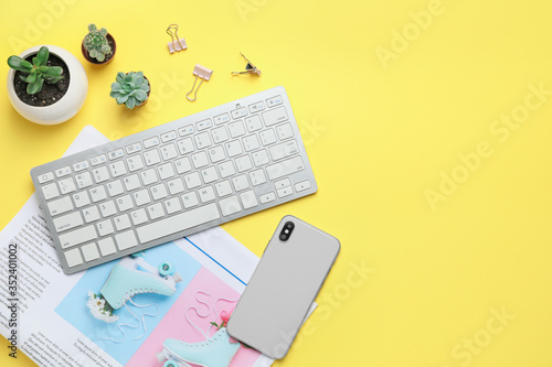 Obraz Computer keyboard with newspaper, and mobile phone on color background - fototapety do salonu