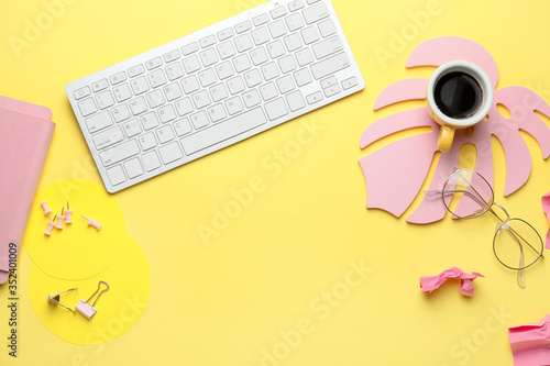 Obraz Computer keyboard with cup of coffee, eyeglasses and stationery on color background - fototapety do salonu