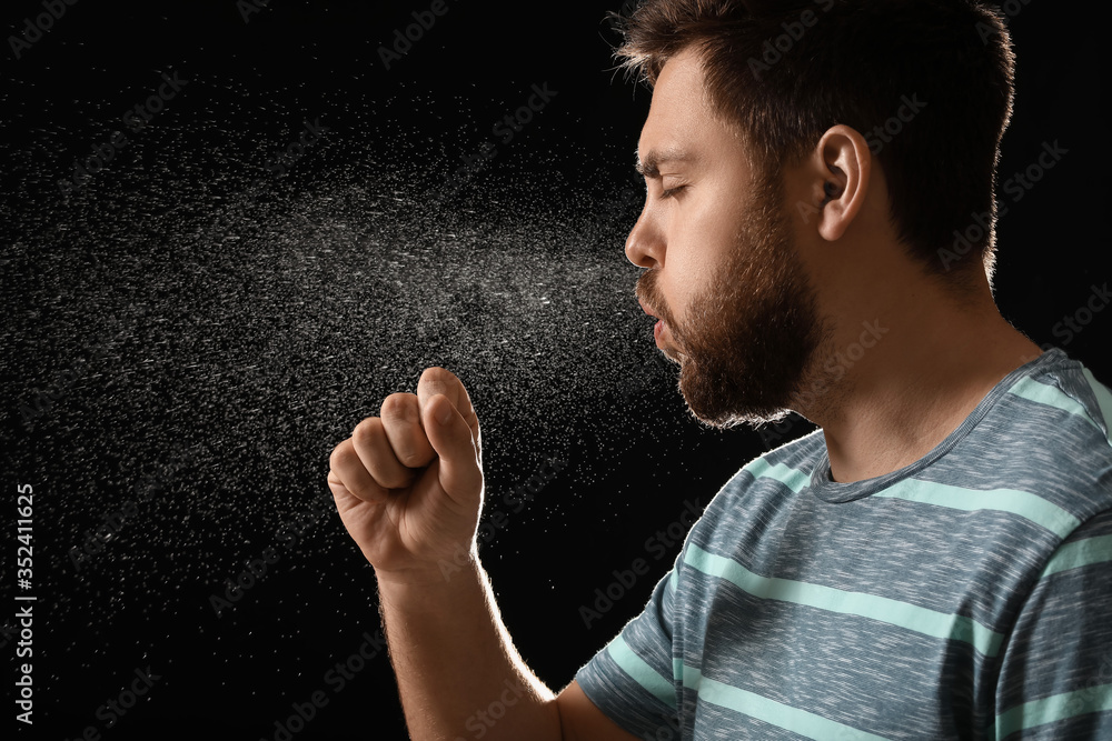 Fototapeta Coughing man on dark background. Concept of epidemic