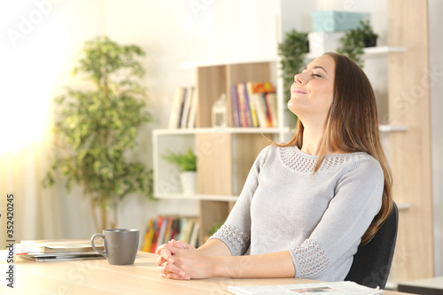 Fotografie, Obraz Woman breathing fresh air sitting on a desk at home