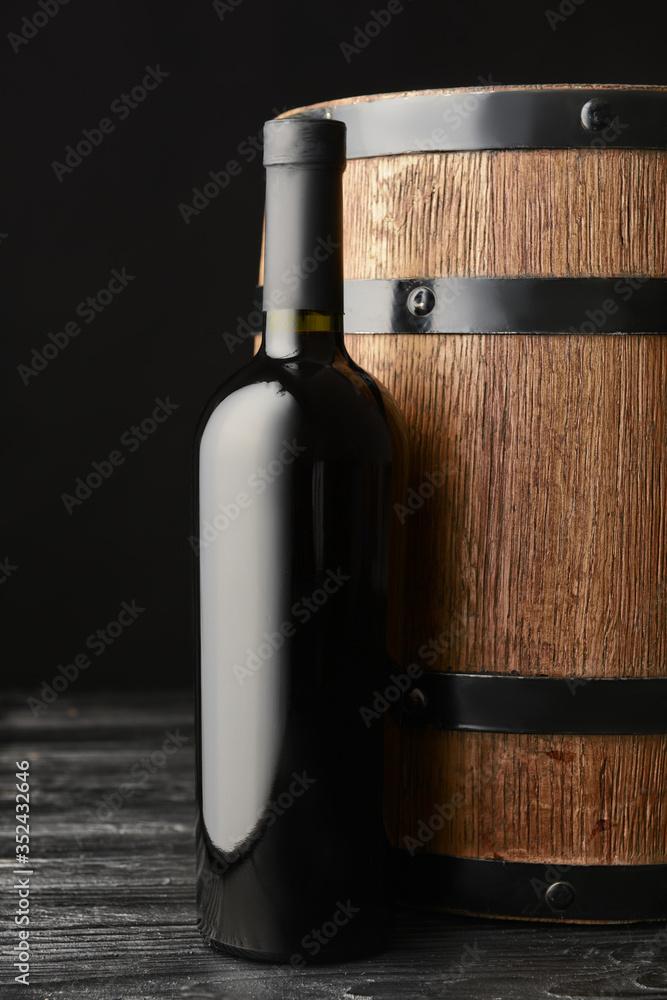 Fototapeta Wooden barrel and bottle of wine on dark background