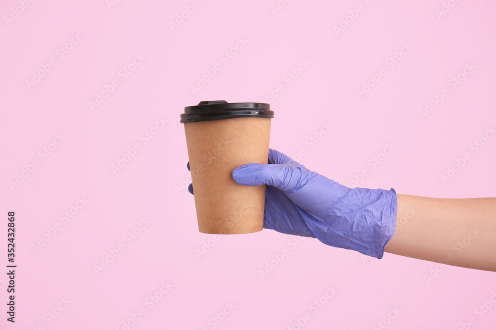 Fototapeta Hand in glove holding takeaway cup for drink on color background