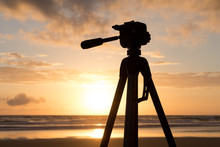 Silhouette Tripod Against Cloudy Sky At Beach During Sunset