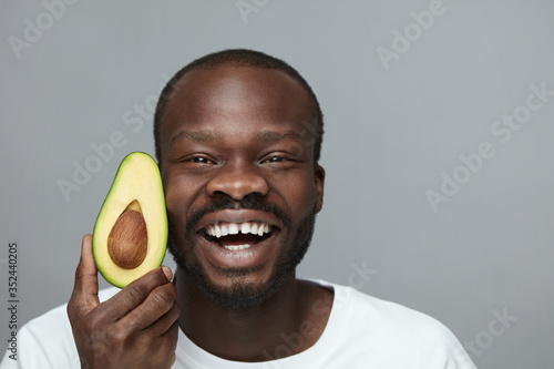 Obraz Avocado For Health. Facial Skincare Treatment With Natural Vitamins. Male African Model Holds Fresh Fruit Near Face. - fototapety do salonu