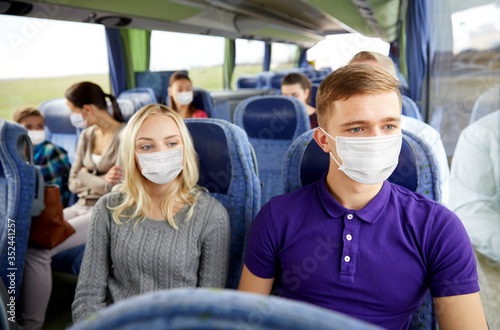 Obraz tourism, healthcare and pandemic concept - couple with group of passengers or tourists wearing face protective medical mask for protection from virus disease in travel bus - fototapety do salonu