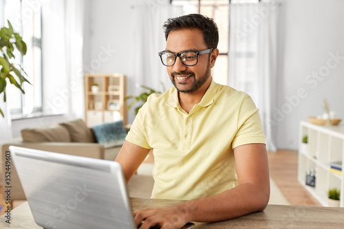 Fototapeta technology, remote job and lifestyle concept - happy indian man in glasses with laptop computer working at home office obraz