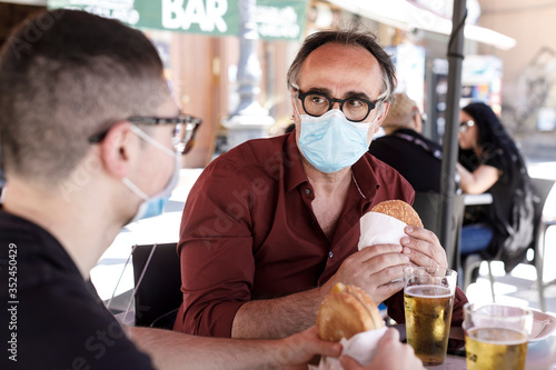 un uomo e un ragazzo mangiano un panino seduti nel tavolino di un bar protetti d Fototapete
