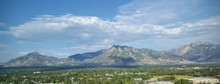 Scenic View Of Rocky Mountains Against Cloudy Sky On Sunny Day