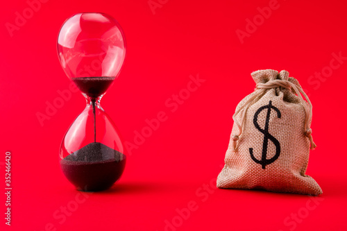 Obraz Close-up view of moneybag account market management stocks shares rate running out of time sand clock counting isolated over bright vivid shine vibrant red color background - fototapety do salonu