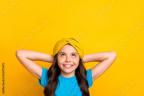 Obraz Closeup photo of beautiful little lady model hold arms behind head resting good mood looking up empty space dreamer wear casual blue t-shirt headband isolated yellow color background - fototapety do salonu