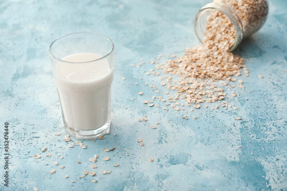 Fototapeta Glass of tasty oat milk on color background