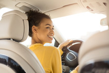Cheerful Black Woman Driving Car Sitting In Automobile, Back View