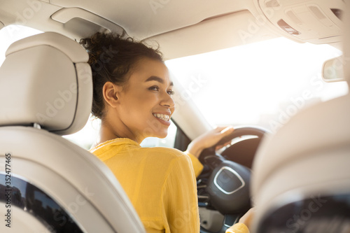 Fotografie, Obraz Cheerful Black Woman Driving Car Sitting In Automobile, Back View