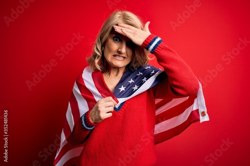 Photo Middle age blonde patriotic woman wearing united states flag celebrating independence day stressed with hand on head, shocked with shame and surprise face, angry and frustrated
