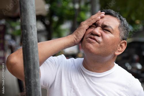 unlucky careless old senior man hitting his head with iron pole; concept of head Canvas Print